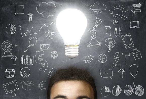 A view of a person's forehead with an illuminated lightbulb above it in front of a background showing a chalkboard covered by diagrams.