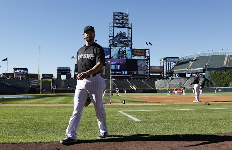 Colorado Rockies first baseman Todd Helton, who has announced that he will retire at the end of the season, heads to the dugout before facing the Boston Red Sox in a baseball game in Denver on Wednesday, Sept. 25, 2013. (AP Photo/David Zalubowski)