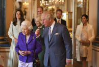 """FILE - In this Tuesday, March 5, 2019 file photo, Britain's Queen Elizabeth II is joined by Prince Charles, the Prince of Wales, and at rear, from left, Kate, Duchess of Cambridge, Camilla, Duchess of Cornwall, Prince William, Prince Harry and Meghan, Duchess of Sussex during a reception at Buckingham Palace, London, to mark the fiftieth anniversary of the investiture of the Prince of Wales. Britain and its royal family are absorbing the tremors from a sensational television interview with Prince Harry and Meghan. The couple said they encountered racist attitudes and a lack of support that drove Meghan to thoughts of suicide. The couple gave a deeply unflattering depiction of life inside the royal household, depicting a cold, uncaring institution that they had to flee to save their lives. Meghan told Oprah Winfrey that at one point """"I just didn't want to be alive anymore."""" Meghan, who is biracial, said that when she was pregnant with son Archie, there were """"concerns and conversations about how dark his skin might be when he's born."""" (Dominic Lipinski/Pool via AP, File)"""