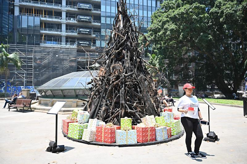 A volunteer collects donations in front of an an installation dubbed 'the Burnt Christmas Tree' to support the Australian Red Cross Disaster Relief and Recovery Fund in Sydney. (Photo: PETER PARKS via Getty Images)