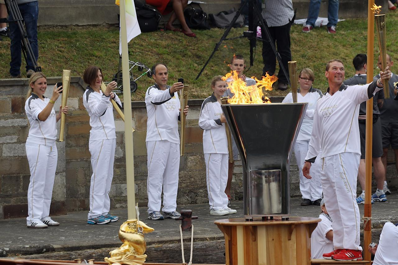 LONDON, ENGLAND - JULY 27:  Olympic rower Matthew Pinsent (R) lights the cauldron on the Queen's rowbarge 'Gloriana' which will carry the Olympic flame along the river Thames from Hampton Court to City Hall on the final day of the London 2012 Olympic Torch Relay on July 27, 2012 in London, England. The Olympic flame is making its way through the capital on the final day of its journey around the UK before arriving in the Olympic Stadium tonight for the Olympic games' Opening Ceremony.  (Photo by Oli Scarff/Getty Images)