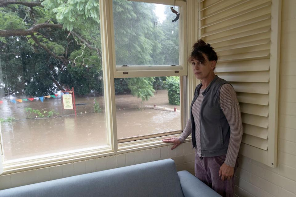 Windsor resident Kelly Miller shows concern as flood waters reach her workplace, a 100 year old property near the Windsor CBD in Sydney.