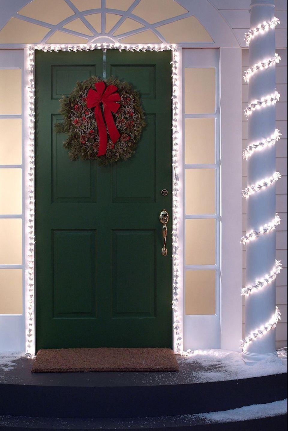 <p>Taking cues from classic candy canes, this festive front door features light-wrapped columns, plus a classic wreath to tie the look together. </p>