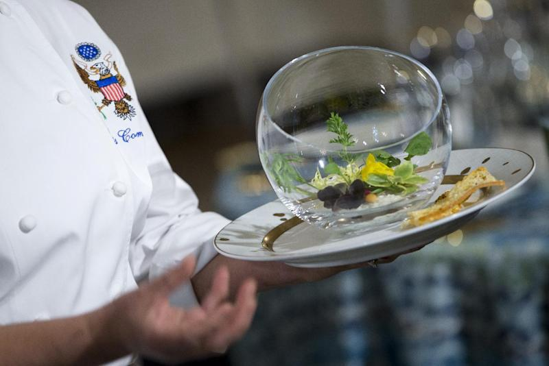 """White House Executive Chef Cris Comerford holds the """"Winter Garden Salad"""" during a press preview in the State Dining Room of the White House in Washington, Monday, Feb. 10, 2014, ahead of Tuesday's State Dinner for French President François Hollande. First lady Michelle Obama's office gave the media, and by extension, the public, a peek at the elegant place settings, colorful flower arrangements and other details of the soiree. At least part of the evening's event will take place in a huge white tent going up on the South Lawn. The salad includes petite mixed radish, baby carrots, and merlot lettuce red wine vinaigrette. (AP Photo/ Evan Vucci)"""