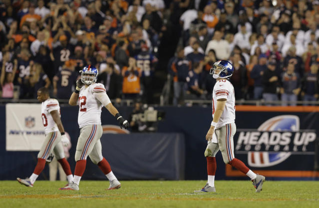 New York Giants quarterback Eli Manning, right, walks off the field after throwing an interception in the fourth quarter of an NFL football game against the Chicago Bears, Thursday, Oct. 10, 2013, in Chicago. The Bears won 27-21. (AP Photo/Nam Y. Huh)