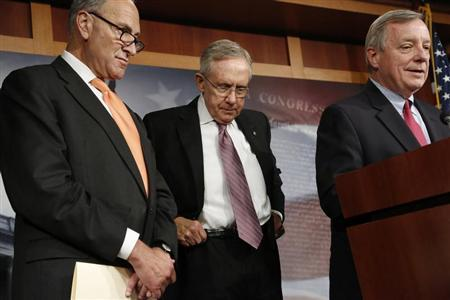 Reid hitches up his belt during a news conference with Schumer and Durbin at the U.S. Capitol in Washington