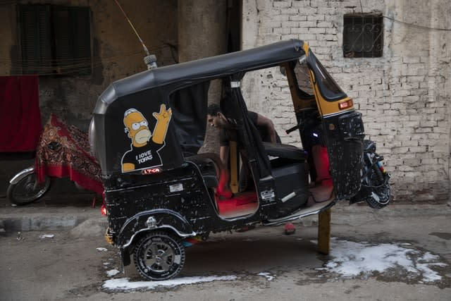 A tuk-tuk driver washes his vehicle in an alleyway of a slum in Cairo, Egypt