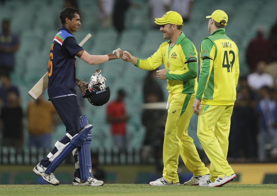 India's Navdeep Saini, left, gestures to Australia's Aaron Finch as Steve Smith watches following the one day international cricket match between India and Australia at the Sydney Cricket Ground in Sydney, Australia, Friday, Nov. 27, 2020.Australia defeated India by 66 runs. (AP Photo/Rick Rycroft)