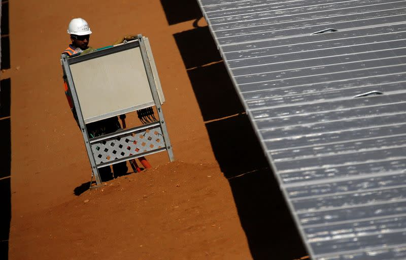 A worker sets up the photovoltaic panels at the Benban plant in Aswan
