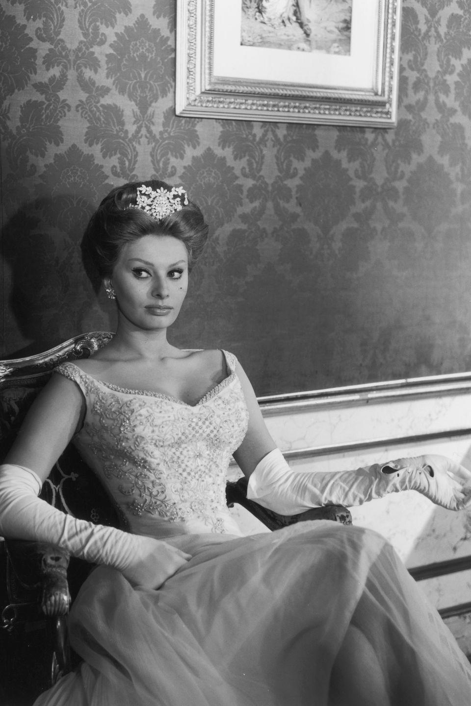 <p>Sophia Loren takes a break from filming in 1960. For <em>A Breath of Scandal, </em>the Italian actress donned a full length ball gown, elbow-length gloves, and a tiara. </p>