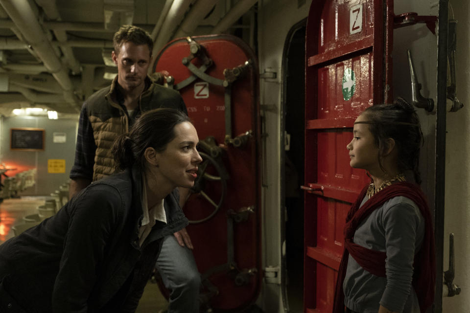 "This image released by Warner Bros. Entertainment shows Alexander Skarsgard, background, Rebecca Hall, foreground left, and Kaylee Hottle in a scene from ""Godzilla vs. Kong."" (Chuck Zlotnick/Warner Bros. Entertainment via AP)"
