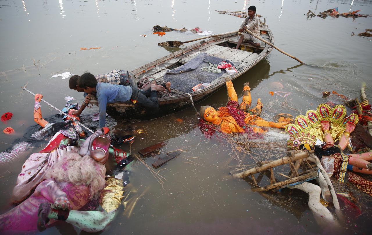 <p>Indian boys pull an idol of Hindu goddess Durga to shore to clean up the temporary water body beside the Ganges river, after immersion of Durga idols by Hindu devotees in Allahabad, India, Saturday, Sept. 30, 2017. (Photo: Rajesh Kumar Singh/AP) </p>