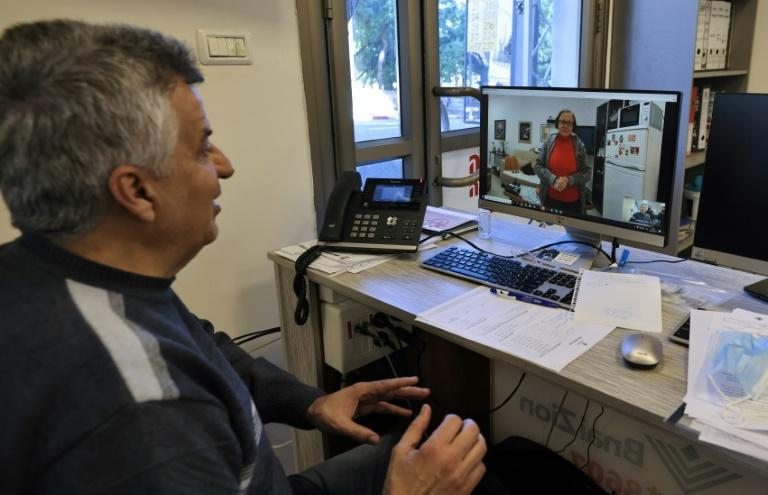 Holocaust survivor Naomie Lichthaus, 86, appears on the screen in a video call with Shimon Shabag of Israel's Yad Ezer La-Haver foundation