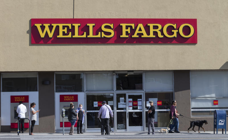 Customer, some wearing face masks, line up outside a Wells Fargo branch in the Atwater Village neighborhood of Los Angeles on Friday, April 3, 2020, during the coronavirus outbreak. (AP Photo/Damian Dovarganes)