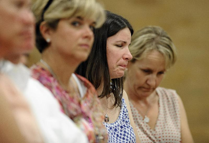 Krista Rekos, center, mother of Sandy Hook School shooting victim Jessica Rekos, reacts during a public forum on the distribution of Newtown donations at Edmond Town Hall in Newtown, Conn., Thursday, July 11, 2013. A community foundation has been tasked with dividing up $11.4 million that was raised with the help of the United Way. At Thursday's meeting, people can comment on the disbursement of $7.7 million that has been set aside for the families of the 26 people who were killed, two wounded teachers and the families of 12 children who escaped. (AP Photo/Jessica Hill)