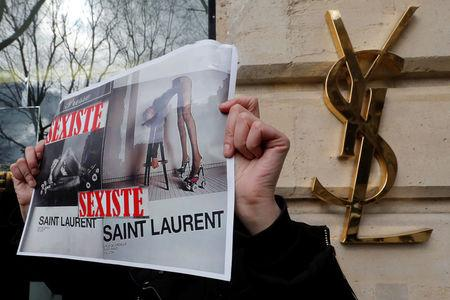 """Activists hold placards which read """"Sexist"""" during a demonstration in front of a Yves Saint Laurent shop in Paris, France, March 7, 2017. REUTERS/Philippe Wojazer"""