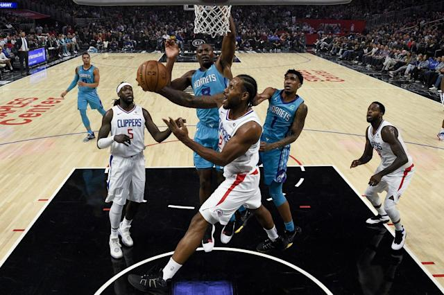 Los Angeles Clippers forward Kawhi Leonard, front, goes up for a shot in front of Charlotte Hornets center Bismack Biyombo during the first half an NBA basketball game in Los Angeles, Monday, Oct. 28, 2019. (AP Photo/Kelvin Kuo)