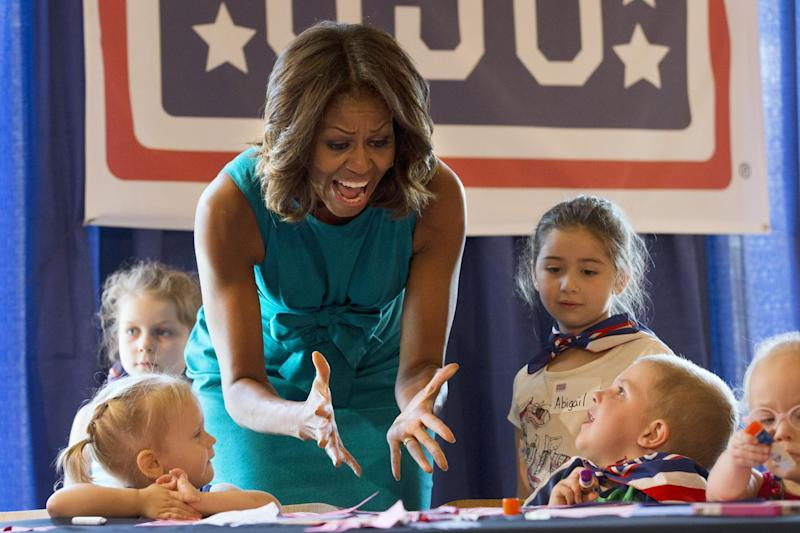 First lady Michelle Obama exclaims over children's artwork during a visit with children at the USO Warrior and Family Center in Fort Belvoir, Va., Wednesday, Sept. 11, 2013, during a service project to commemorate the Sept. 11th National Day of Service and Remembrance at Food and Friends. (AP Photo/Jacquelyn Martin)