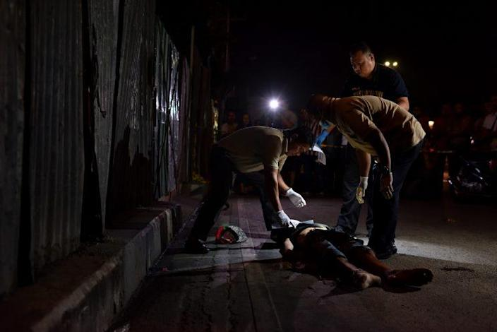 Police investigators inspect the body of a still-unidentified victim bound, wrapped in packaging tape, and dumped in a main thoroughfare in Pasay city, Philippines. (Photo: Jes Aznar/Getty Images)
