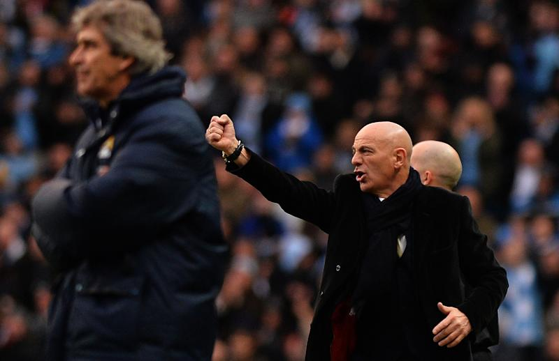 Watford manager Giuseppe Sannino (R) gestures behind Manchester City manager Manuel Pellegrini as their teams clash at Manchester's Etihad Stadium on January 25, 2014