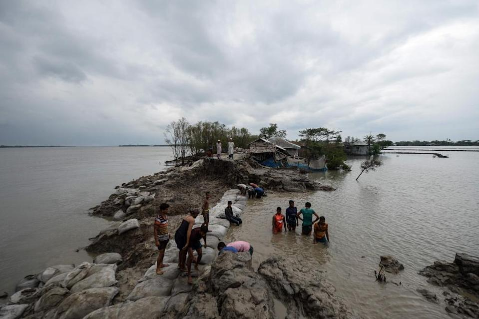 Volunteers and residents work to repair a damaged dam following the landfall of cyclone Amphan in Burigoalini.