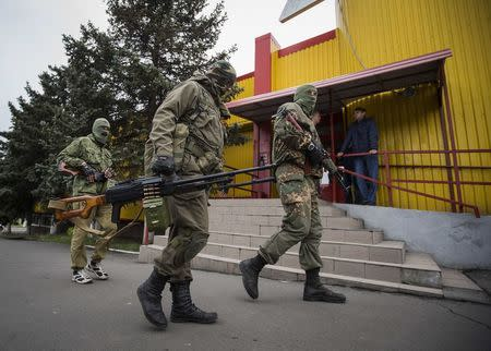 Armed pro-Russian separatists walk past a shop at a town center in Snizhnye in eastern Ukraine