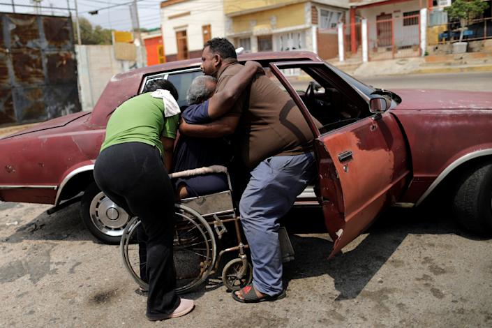 Elimenes Fuenmayor, 65, who has kidney disease, is helped by his sons, as he leaves his house to go to the dialysis center during a blackout in Maracaibo, Venezuela. (Photo: Ueslei Marcelino/Reuters)