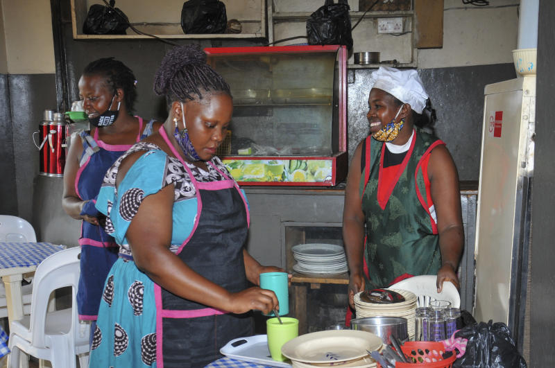 In this photo taken Saturday, June 20, 2020, Rebecca Nakamanya, right, and colleague Namara Grace, center, work at a restaurant near a bus terminal in capital Kampala, Uganda. The COVID-19 pandemic means that millions of women in Africa and other developing regions could lose years of success in contributing to household incomes, asserting their independence and expanding financial inclusion. (AP Photo/Ronald Kabuubi)