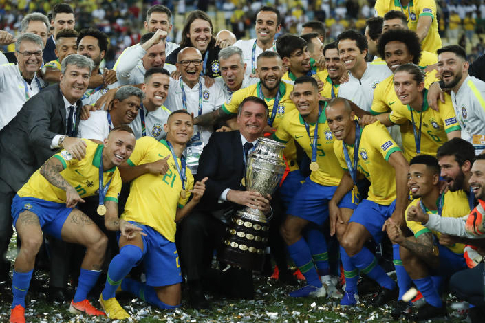 Brazil's President Jair Bolsonaro holds the trophy as he celebrates with Brazil players after they won 3-1 the final soccer match of the Copa America against Peru at the Maracana stadium in Rio de Janeiro, Brazil, Sunday, July 7, 2019. (AP Photo/Victor R. Caivano)