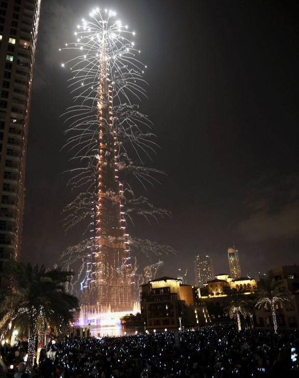 Revellers watch fireworks illuminating over Burj Khalifa in Dubai on January 1, 2013. Thousands of people gathered to celebrate the New Year at midnigh. AFP PHOTO/STR