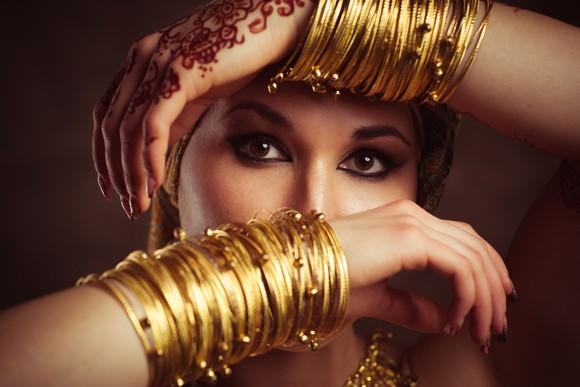 A woman hiding her face behind arms covered with gold bangles