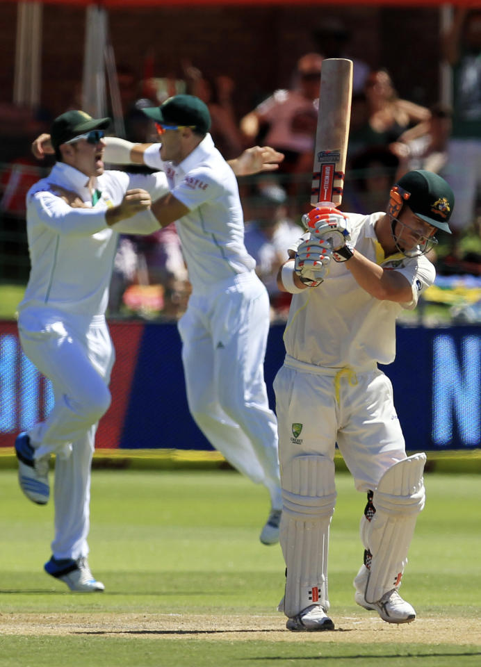 Australia's batsman David Warner, right, reacts as South Africa's captain Graeme Smith, left, and teammate Faf du Plessis, center, celebrate his dismissal on the third day of their second cricket test match at St George's Park in Port Elizabeth, South Africa, Saturday, Feb. 22, 2014. (AP Photo/ Themba Hadebe)