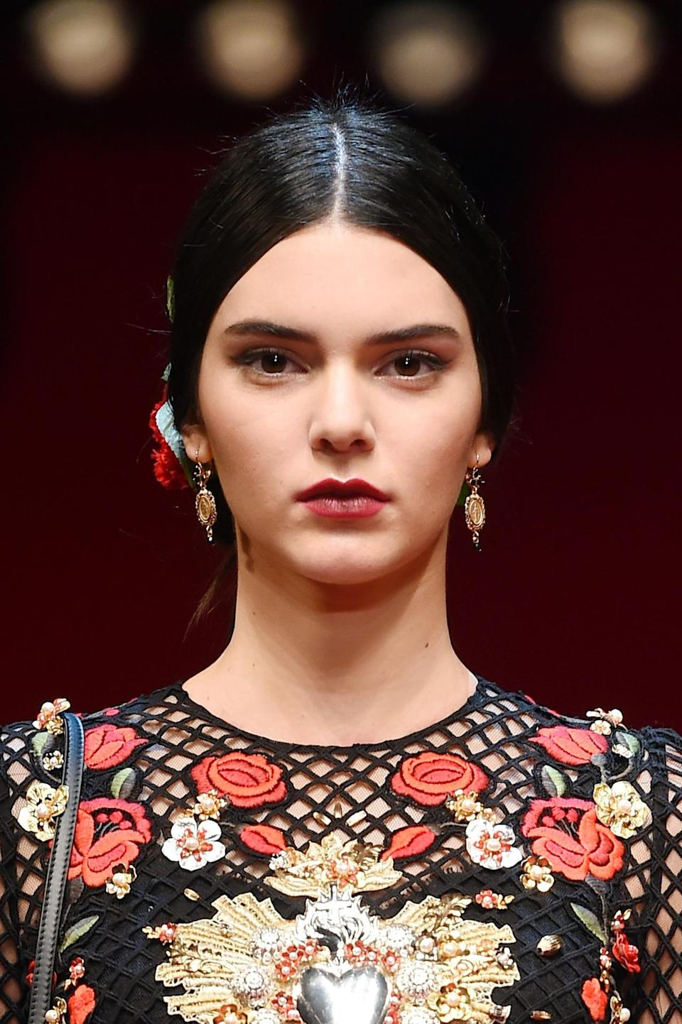 <p>At Dolce & Gabbana Spring 2015 in Milan, Jenner channeled Spanish bullfighters with cherry red lips and a tight centerpart chignon. <i>(Photo: Getty Images)</i></p>