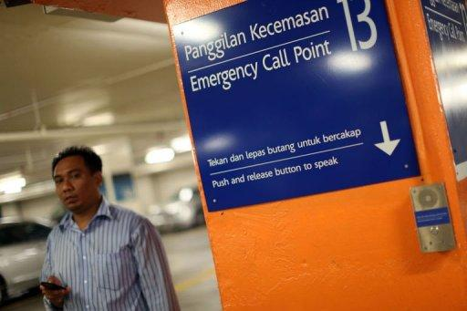 A shopper walks past an emergency call point (R) at the car park of a shopping mall in Kuala Lumpur on August 8. The fear of crime is soaring in Malaysia as personal tales of abduction, assault and robbery go viral online, upping pressure on authorities to respond and triggering scrutiny of official claims that offences are down