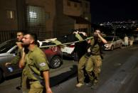 Members of the military carry injured people outside a synagogue in Givat Zeev
