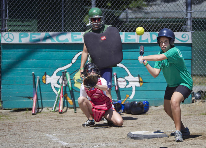 Laila, from Cairo, Egypt, bats during a softball game at the Seeds of Peace camp in Otisfield, Maine, Friday, July 5, 2013. The summer camp brings together young people from countries at conflict. (AP Photo/Robert F. Bukaty)