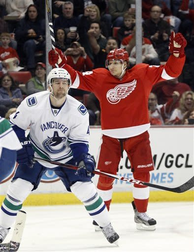 Detroit Red Wings center Damien Brunner, right, who had an assist on the play, celebrates a goal by right wing Daniel Cleary while Vancouver Canucks defenseman Keith Ballard, left, reacts in the second period of an NHL hockey game Sunday, Feb. 24, 2013, in Detroit. (AP Photo/Duane Burleson)