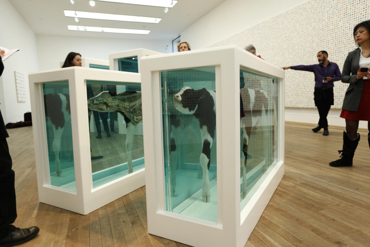 "People look at part of the British artist Damien Hirst's 2007 exhibition copy piece of the 1993 original ""Mother and Child Divided"", composed of a cow and a calf sliced in half in glass tanks of formaldehyde, during a media preview of the first substantial survey show of his work in the UK at the Tate Modern gallery in London, Monday, April 2, 2012. The exhibition, timed for the culmination of the Cultural Olympiad and due to open to the public on Wednesday, showcases over 70 of Hirst's works since he first came to public attention in 1988. (AP Photo/Matt Dunham)"
