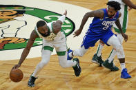 Boston Celtics guard Jaylen Brown, left, dribbles up court under pressure from Los Angeles Clippers guard Patrick Beverley (21) in the third quarter of an NBA basketball game, Tuesday, March 2, 2021, in Boston. (AP Photo/Elise Amendola)