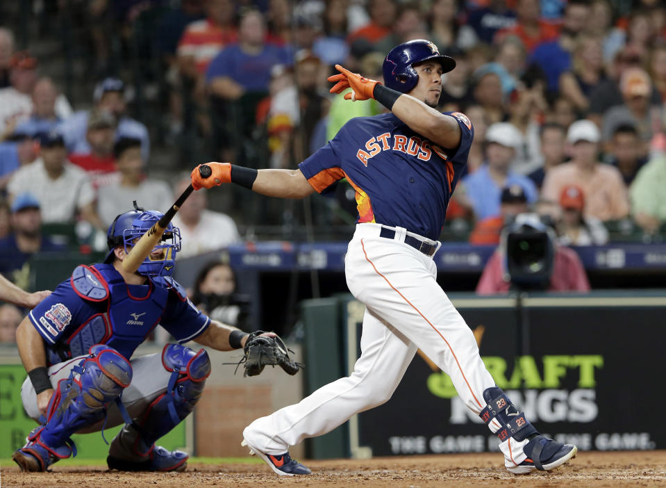 Houston Astros left fielder Michael Brantley, right, watches his hit for a single in front of Texas Rangers catcher Jeff Mathis, right during the third inning of a baseball game Sunday, July 21, 2019, in Houston. (AP Photo/Michael Wyke)