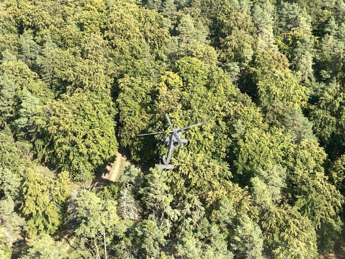 Image: A Boeing AH-64 Apache helicopter hovering over woodland during a ten-day, multi-national military exercise at the U.S. Army's Hohenfels training area (Edward Kiernan / NBC News)