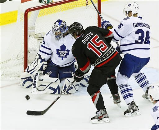 Carolina Hurricanes' Tuomo Ruutu (15), of Finland, has his shot blocked by Toronto Maple Leafs goalie James Reimer (34) with Maple Leafs' Carl Gunnarsson (36), of Sweden, defending during the second period of an NHL hockey game in Raleigh, N.C., Thursday, Dec. 29, 2011. (AP Photo/Karl B DeBlaker)
