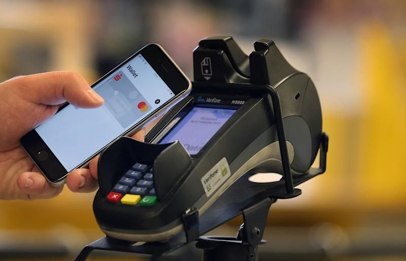 A smartphone is held at the payment terminal at the checkout of a supermarket.
