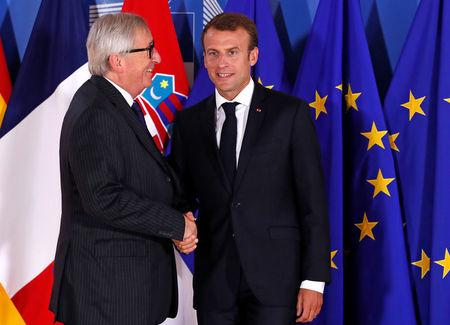 French President Emmanuel Macron is welcomed by European Commission President Jean-Claude Juncker at the start of an emergency European Union leaders summit on immigration at the EU Commission headquarters in Brussels, Belgium June 24, 2018.  REUTERS/Yves Herman/Pool