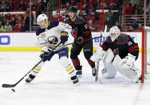Buffalo Sabres' Sam Reinhart (23) tries to get a shot against Carolina Hurricanes goalie Curtis McElhinney (35) and Hurricanes' Andrei Svechnikov (37), of Russia, during the first period of an NHL hockey game in Raleigh, N.C., Saturday, March 16, 2019. (AP Photo/Gerry Broome)