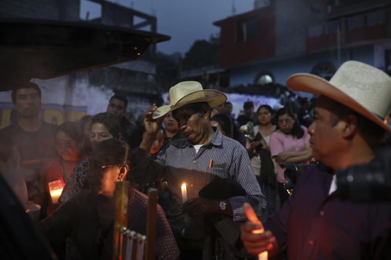 Mourners, some carrying candles, gather around the hearse bringing the body of Maricela Vallejo, the slain 27-year-old mayor of Mixtla de Altamirano, to her aunt's house for her wake, in Zongolica, Veracruz state, Mexico, Thursday, April 25, 2019. Vallejo, her husband, and a driver were assassinated Thursday by multiple gunmen as they drove along a highway. (AP Photo/Felix Marquez)