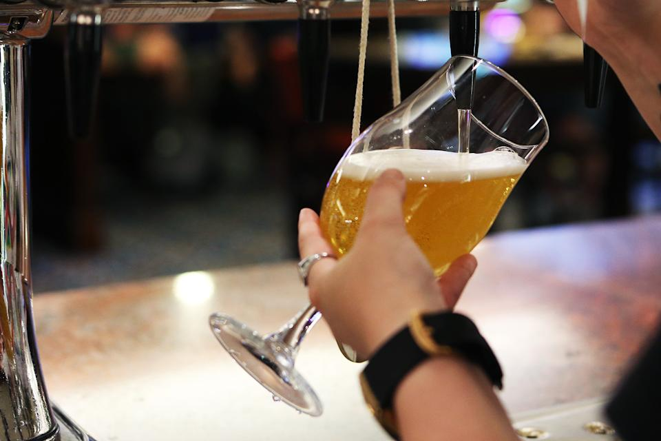 MANCHESTER, ENGLAND - JULY 19: A member of staff pours a pint for a customer at Wetherspoons pub The Moon Under Water on July 19, 2021 in Manchester, England. As of 12:01 on Monday, July 19, England will drop most of its remaining Covid-19 social restrictions, such as those requiring indoor mask-wearing and limits on group gatherings, among other rules. These changes come despite rising infections, pitting the country's vaccination programme against the virus's more contagious Delta variant. (Photo by Charlotte Tattersall/Getty Images)