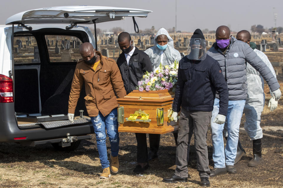 Family members and funeral workers in a protective gear, carry the coffin of nurse Duduzile Margaret Mbonane who died from COVID-19, during her funeral, in Thokoza east of Johannesburg, South Africa, Thursday, July 23, 2020. One of the country's nurses was buried Thursday, the latest of more than 5,000 infected health workers across South Africa. Mbonane died just a month before her retirement, her husband said. (AP Photo/Themba Hadebe)