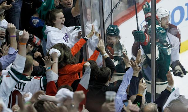Minnesota Wild center Mikael Granlund (64), of Finland, pounds on the glass in front of fans after scoring the game-winning goal against Colorado Avalanche goalie Semyon Varlamov during overtime of Game 3 of an NHL hockey first-round playoff series in St. Paul, Minn., Monday, April 21, 2014. The Wild won 1-0 in overtime. (AP Photo/Ann Heisenfelt)