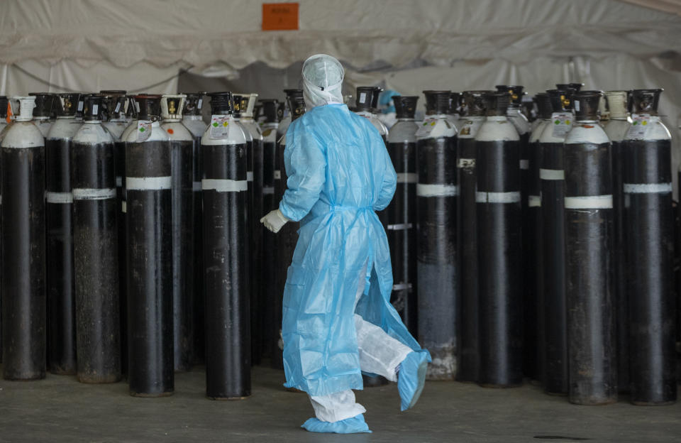 A health worker in a protective suit runs past oxygen cylinders in a makeshift emergency unit at Steve Biko Academic Hospital in Pretoria, South Africa, Monday, Jan. 11, 2021, which is battling an ever-increasing number of Covid-19 patients. (AP Photo/Themba Hadebe)